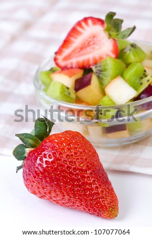 Strawberry and fruit salad in white plate on tablecloth, close up
