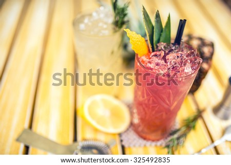strawberry and pineapple alcoholic beverage, served cold with ice at bar. Cocktail drinks with lime, pineapple and alcohol as refreshment drinks on a summer day