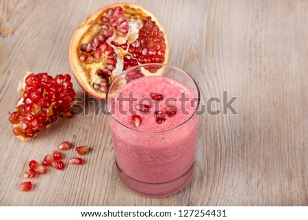 Strawberry and pomegranate healthy smoothie. Isolated on wooden background