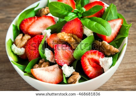 Strawberry and spinach salad with feta cheese and walnuts, organic heathy food.