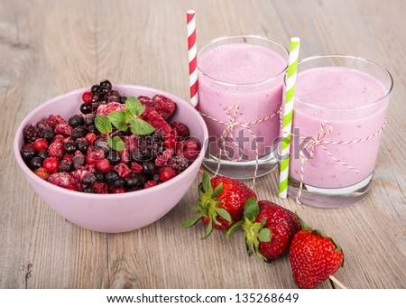 Strawberry and wild berry healthy smoothie drink. On wooden background.