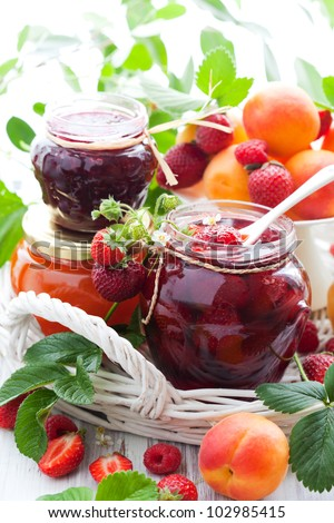 strawberry,apricot, raspberry jam in a jars and fresh berries