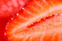 Strawberry background. Blurred natural red background. Texture of strawberry berries. Beautiful sliced strawberries close-up. Horizontal, close-up, nobody. Healthy eating concept.