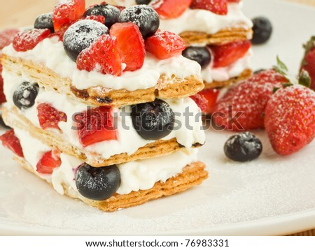 Strawberry-blueberry mille feuille with whipped sour cream. Shallow dof.