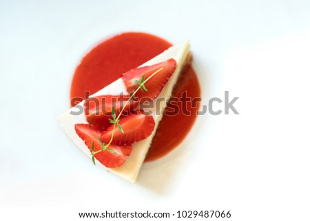 strawberry cheese cake with slice fresh strawberry topping on white dish background,sweet dessert on table,selective focus on strawberry.