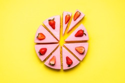 Strawberry cheesecake sliced in unequal pieces, on a yellow seamless background. Flat lay with no-bake strawberry cake. Berry gelatine creamy dessert