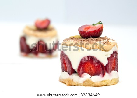 Strawberry cheesecake with mascarpone cream decorated with chocolate chips and a half a strawberry