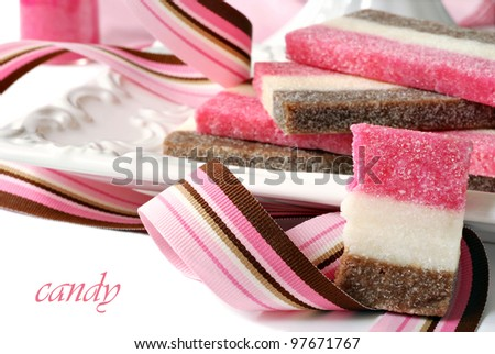 Strawberry, chocolate, and vanilla coconut candy on ceramic plate with color coordinated ribbon.  Macro with shallow dof.  (Text is on solid white and easy to remove.)