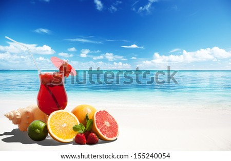 strawberry cocktail and tropical fruit on the beach