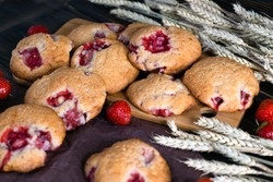 Strawberry cookies on a table with fresh strawberries and spikelets.