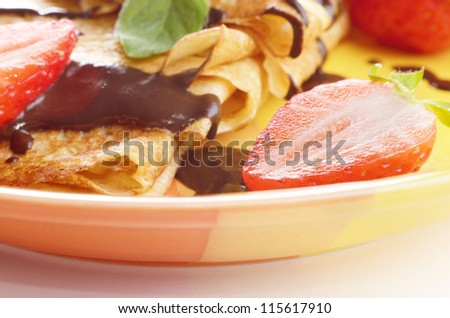 Strawberry crepes with chocolate syrup and mint closeup photo