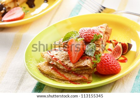 Strawberry crepes with syrup, figs and mint on the table