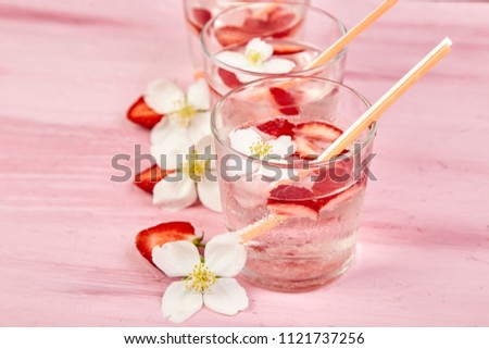 Strawberry detox water with jasmine flower. Summer iced drink or tea. Lemonade with berry. Flavored Water in glasses with Fresh Strawberry. Diet.