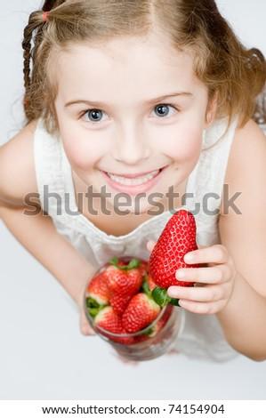 Strawberry fruits - girl eating strawberries - stock photo
