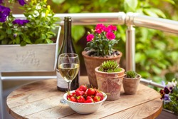Strawberry, glass of wine and flowers on small wooden table on beautiful terrace or balcony