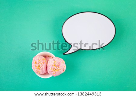 Strawberry ice cream  scoops in white bowl with topping on aquamarine background, top view