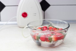 strawberry in a bowl with water with a round ozonating stone. Tubes leading to oxygen pump and ozone generator. ozonation fruit. Food disinfection with ozon