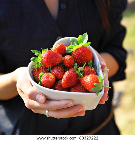 strawberry in heart shape bowl with hand