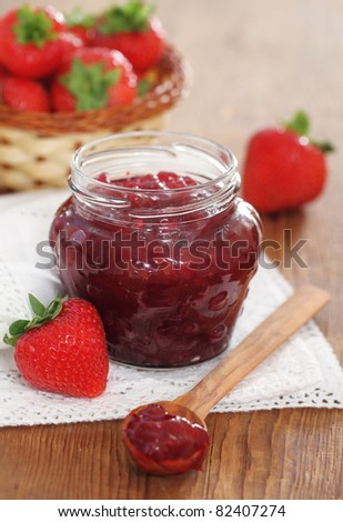 Strawberry jam and fresh strawberries on the wooden table