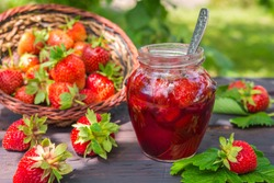 Strawberry jam and juicy ripe strawberries on a wooden table in the garden on a summer sunny afternoon in a rustic style, the concept of gardening, healthy organic vitamin nutrition