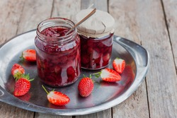 Strawberry jam in a glass jar with some fresh strawberry on steel vintage plate on wooden old rustic table. Homemade strawberry marmelade and fruits. Selective focus.