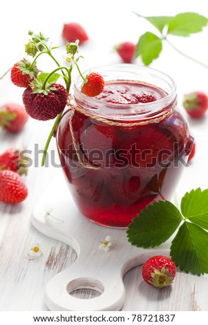 strawberry jam in a jar and fresh berries on the wooden table