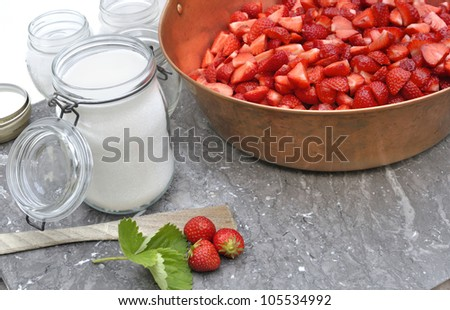 Strawberry jam in jar with sugar for making jam