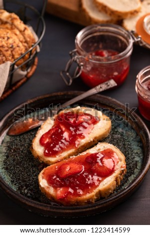 Strawberry jam preserves on buttered toast on speckled unique plate with breadbasket breadboard swing top preserving jar with selective focus.