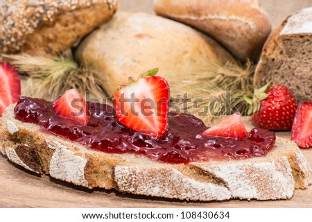 Strawberry Jam with fresh fruits on rustic background