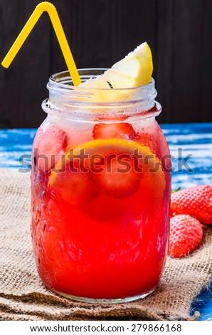 Strawberry lemonade, beverage.Fruit infused water with strawberries and lemon in mason jar.