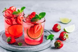 Strawberry lime lemonade with fresh mint and ice in glass jar. Summer refreshing drink.
