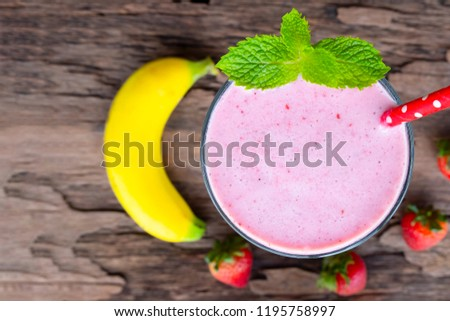 Stock Photo strawberry mix banana  smoothies red colorful fruit juice milkshake blend beverage healthy high protein the taste yummy In glass,drink episode morning on wood background from top view.