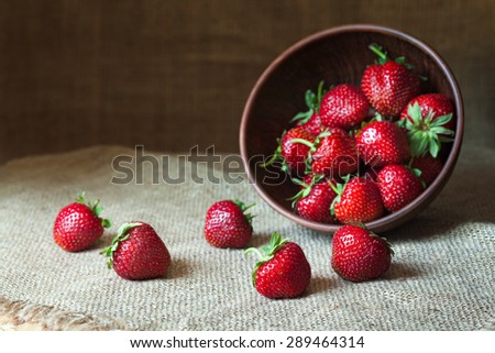 Strawberry natural healthy nutrition organic food in rustic clay dish on vintage kitchen background. Vegetarian, full of vitamin dessert. Dark food photo, rustic style, natural light.