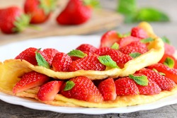 Strawberry omelette. Fried omelette filled with fresh strawberries and garnished with mint on a plate. Fresh strawberries on old wooden table. Sweet breakfast omelette recipe. Closeup