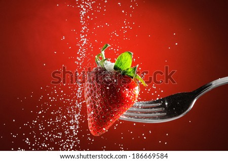 Strawberry on a fork punctured falling sugar with red background detail