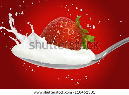 strawberry on the spoon and milk splash - stock photo