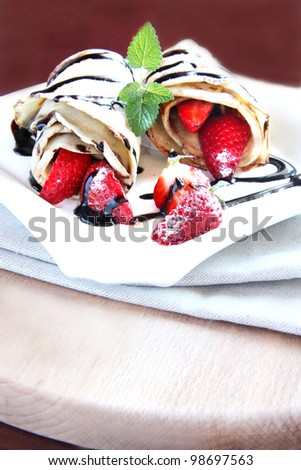 Strawberry pancakes with sugar icing and chocolate topping