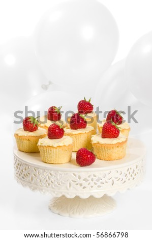 Strawberry party cupcakes on pretty cake stand with balloons in background