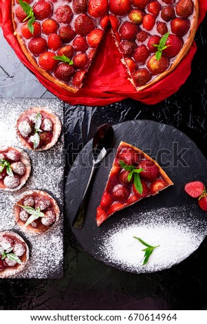 Strawberry pie and tart on black slate plate. Mix desserts. Top view