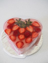strawberry pudding, pudding with heart shape and fresh strawberry fruit on the top and strawberry jelly as bottom layer. delicious, unique, and beautiful. grainy and gritty textured. white isolated