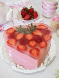 strawberry pudding, pudding with heart shape and fresh strawberry fruit on the top and strawberry jelly as bottom layer. delicious, unique, and beautiful. grainy and gritty textured. blurry background