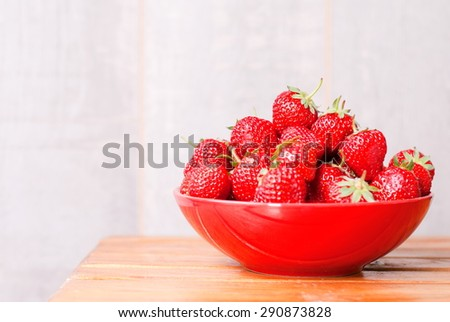 Strawberry red plate on  table, side view