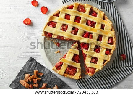 Strawberry rhubarb pie with a piece on table