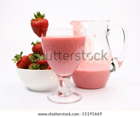 Strawberry shake in a glass and in a jug and strawberries in a bowl on white background