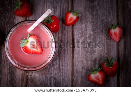 Strawberry smoothie in glass jar over old wood table Vintage effect with intentional vignette
