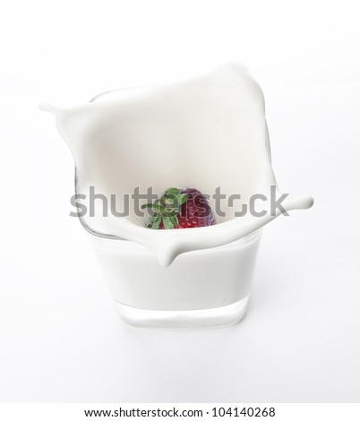 Strawberry splash of milk in a glass on a white background