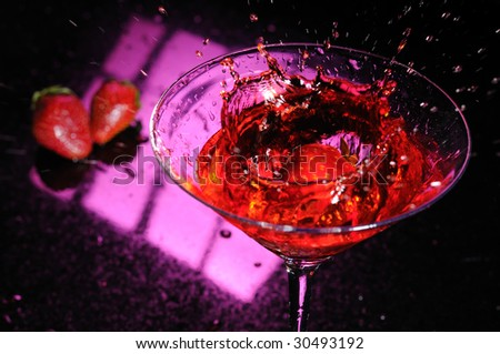 Strawberry splashing down in a martini glass filled with a red liquid