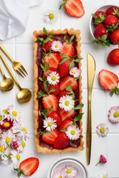 Strawberry tart with berry jelly decorated with fresh berries and daisy flowers. Top view. Selective focus