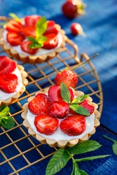 Strawberry tarts, small shortbread tarts with the addition of sweet cream cheese, fresh strawberries and mint on cooling tray on a dark blue table. A delicious homemade strawberry cake, fruit dessert