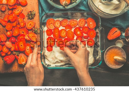 Strawberry tiramisu cake making. Womans female hands laid strawberries on the cake on dark rustic wooden background, top view. Italian food concept #437610235